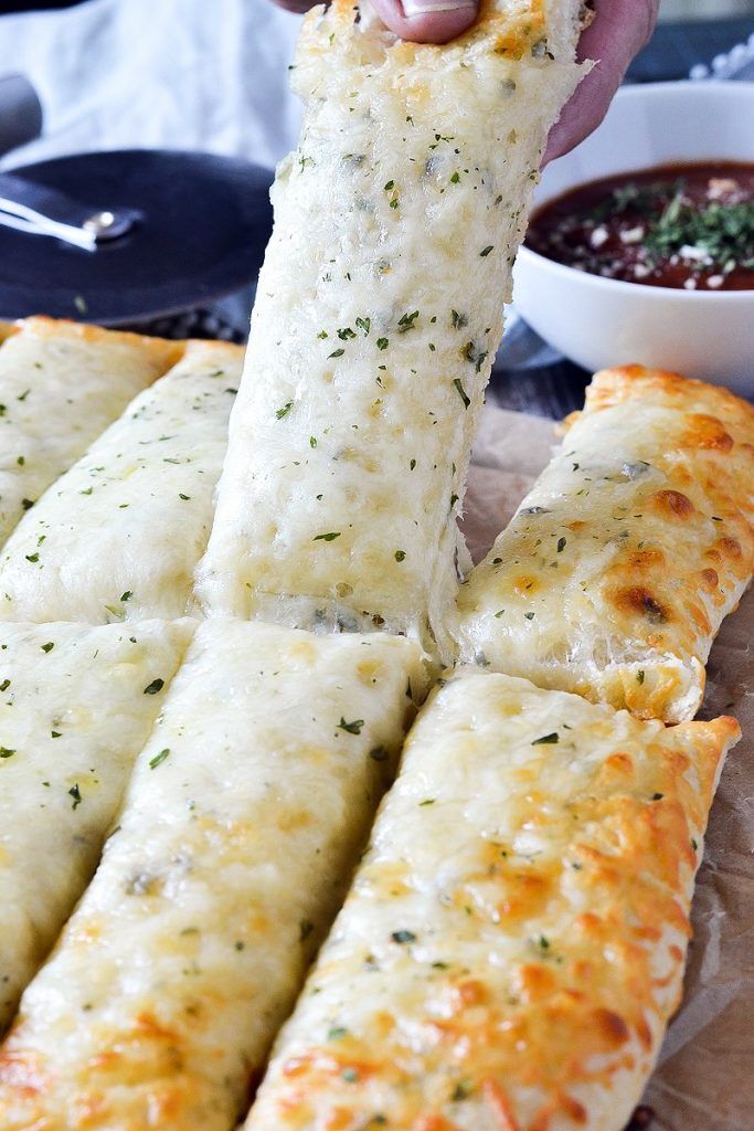 A cheesy garlic breadstick being lifted from the plate.