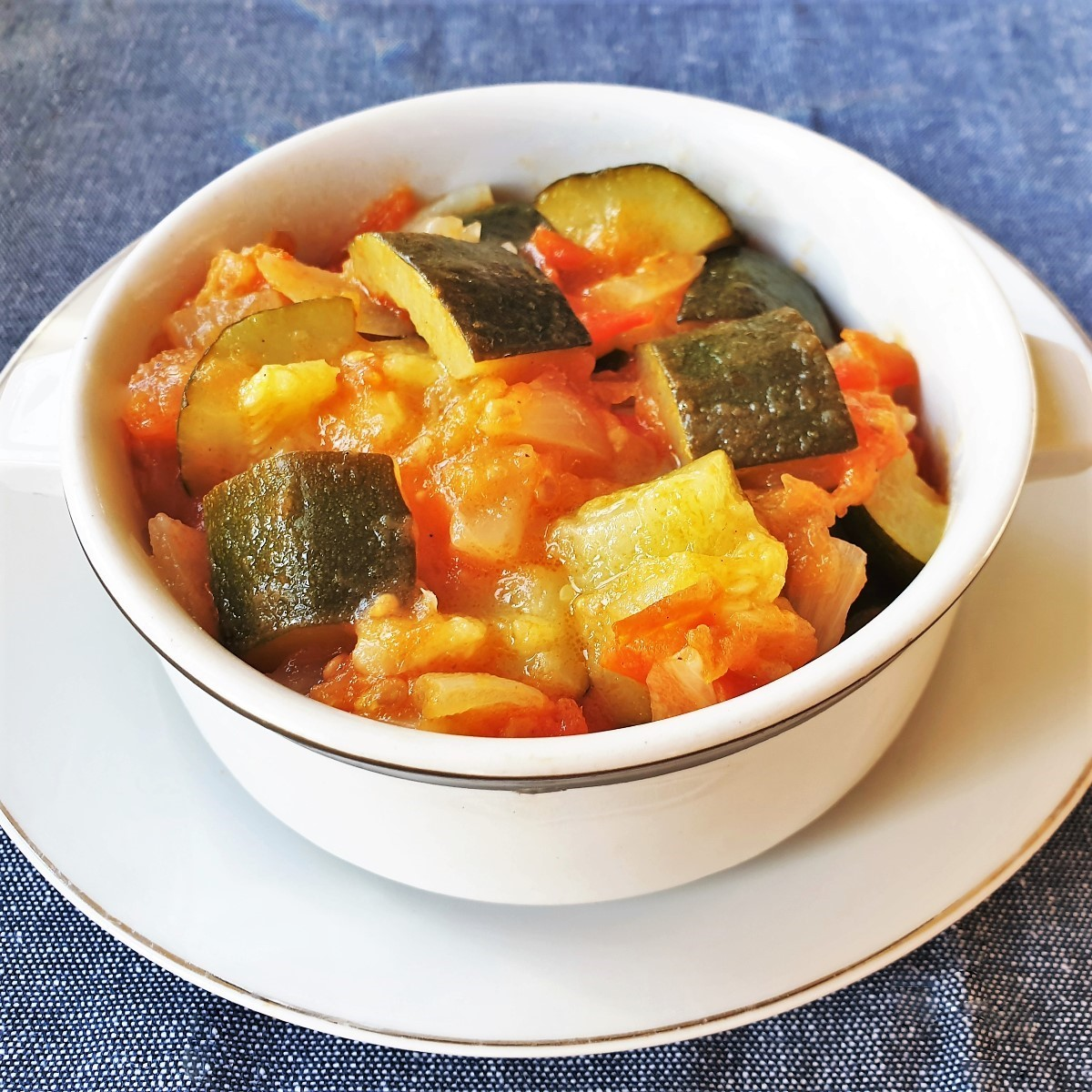 A dish of baby marrows cookin in tomatoes and onions.