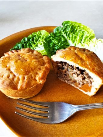 Two mini beef and onion pies on a plate with lettuce.