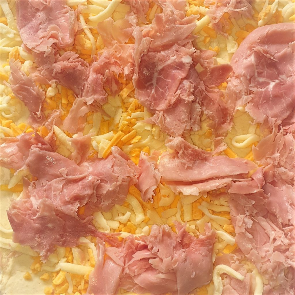 2-ingredient dough rolled out and covered with ham and cheese