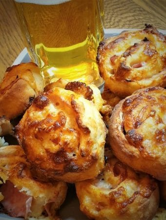 A plate of ham and cheese pinwheels with a glass of beer