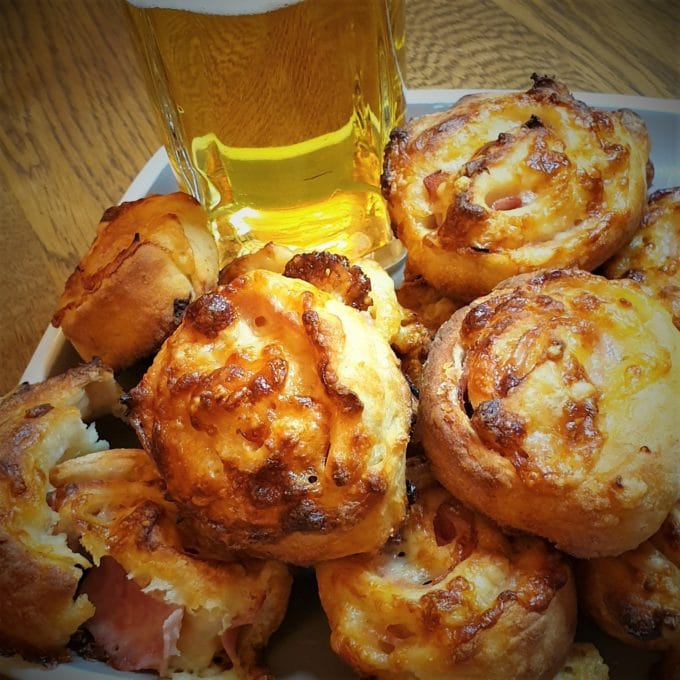 A plate of ham and cheese pinwheels, with a glass of beer.