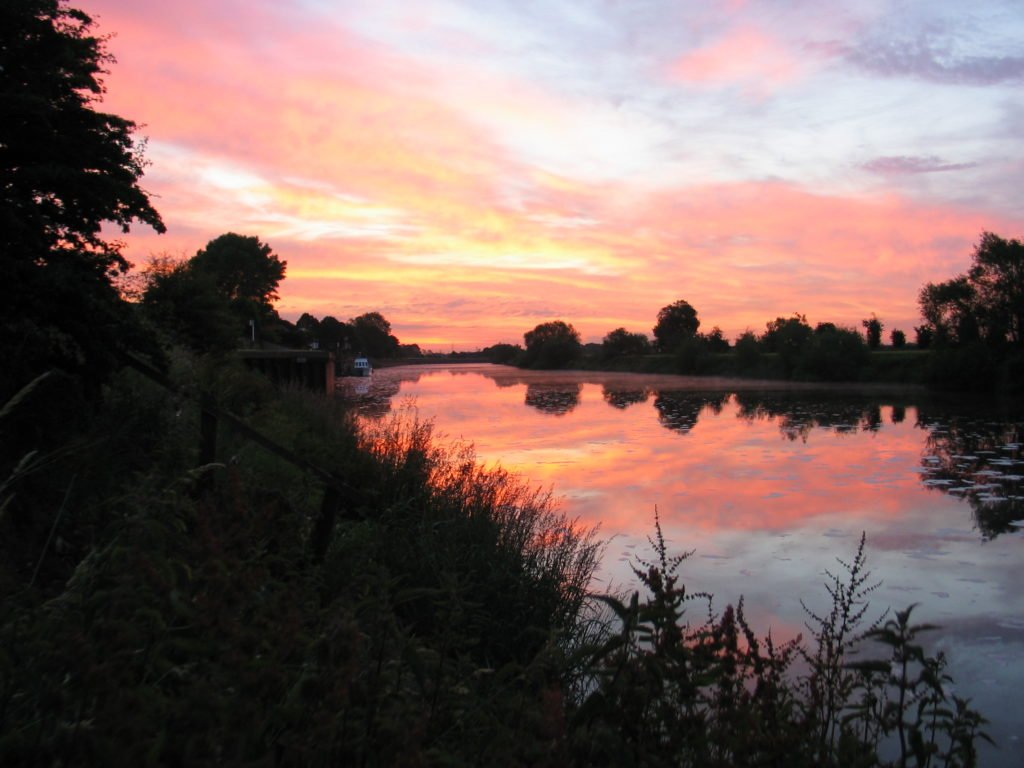 A pink dawn sky reflected in the water of the River Trent