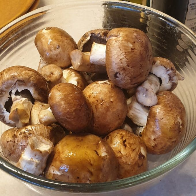 A pile of mushrooms soaking in balsamic vinegar an garlic