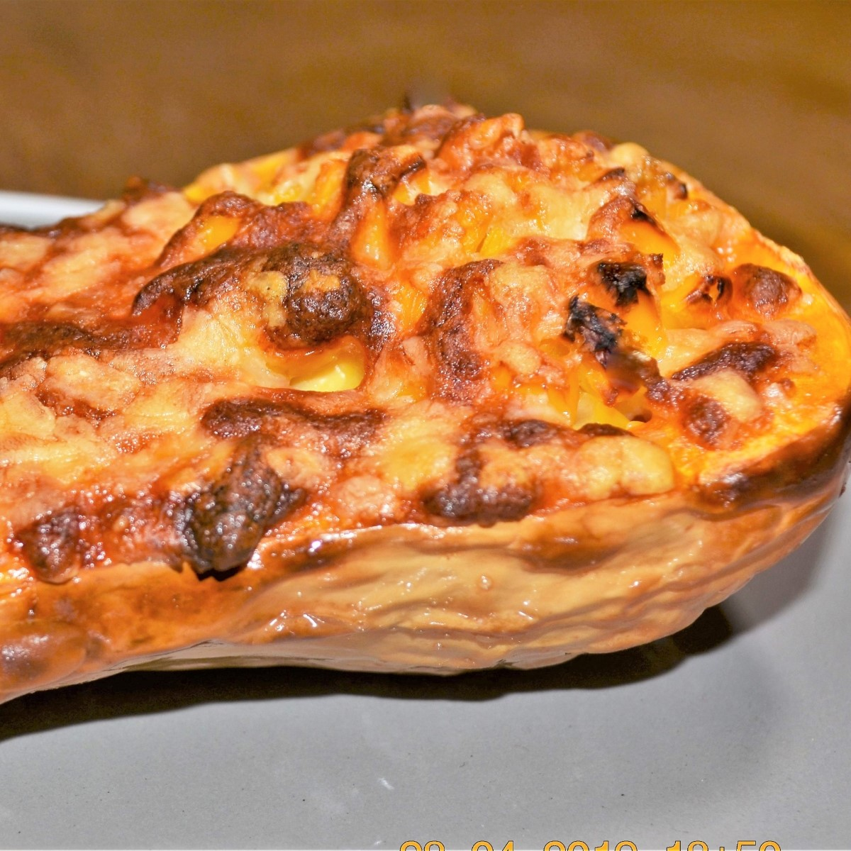 Half a baked butternut, stuffed with cheese and corn, on a plate.