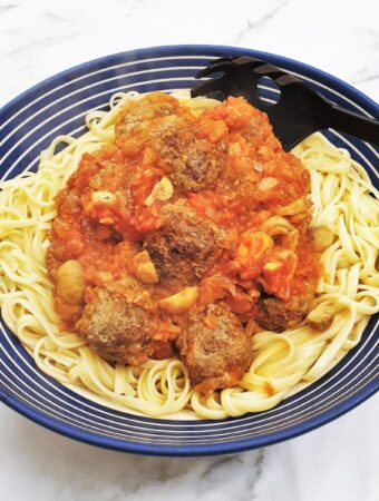 Spicy meatballs in homemade tomato sauce on a bed of spaghetti.