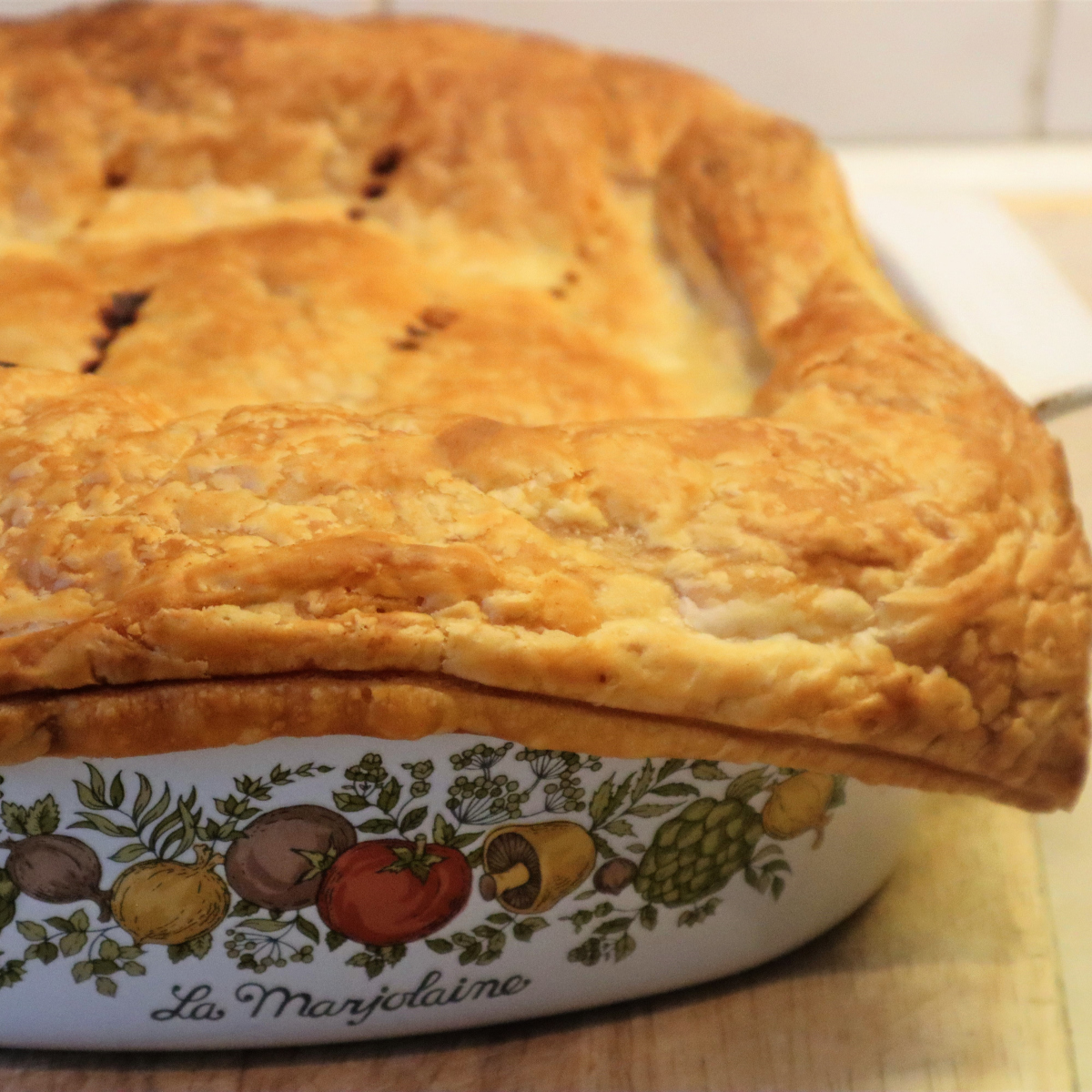 A layer of cooked puff pastry over a steak and kidney pie.