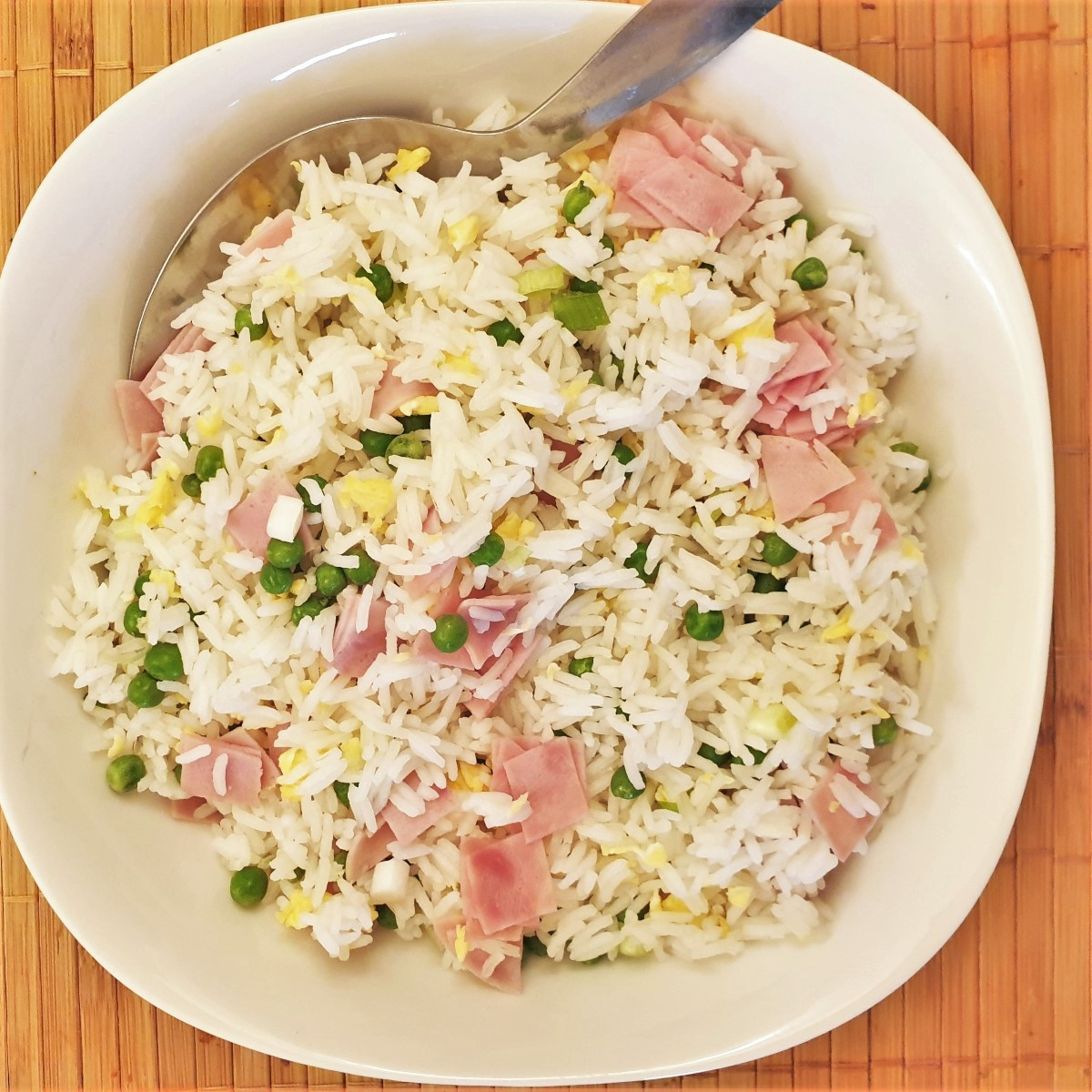Overhead shot of a serving bowl filled with egg fried rice with egg, chopped ham and peas