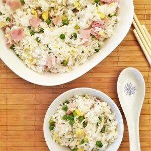 A bowl of egg fried rice next to the serving dish.
