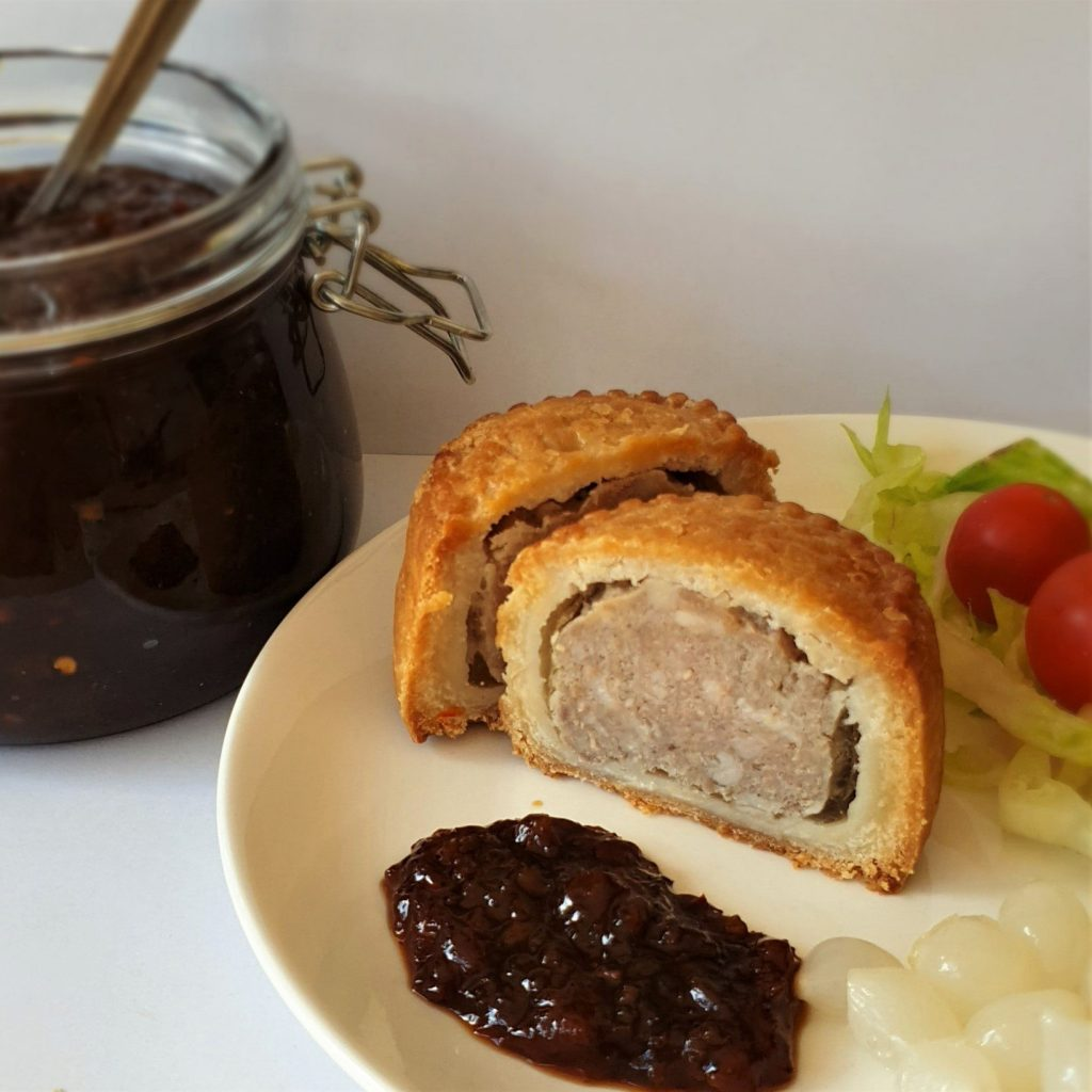 A pork pie on a plate with a spoonful of chutney