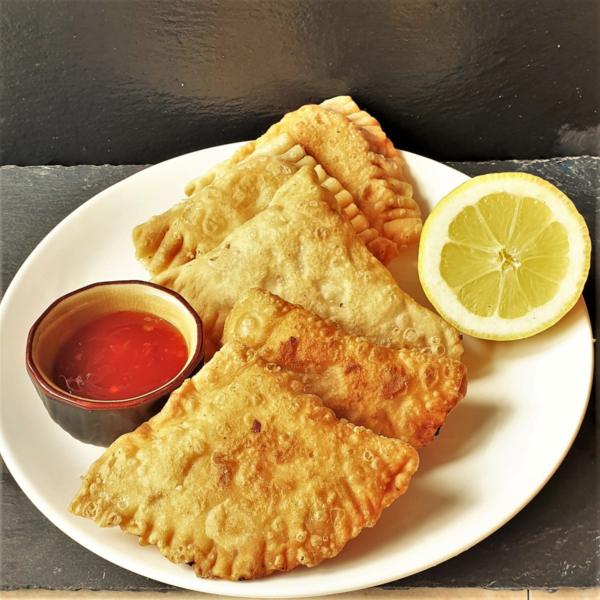 4 samosas on a plate with a slice of lemon and a dipping sauce.