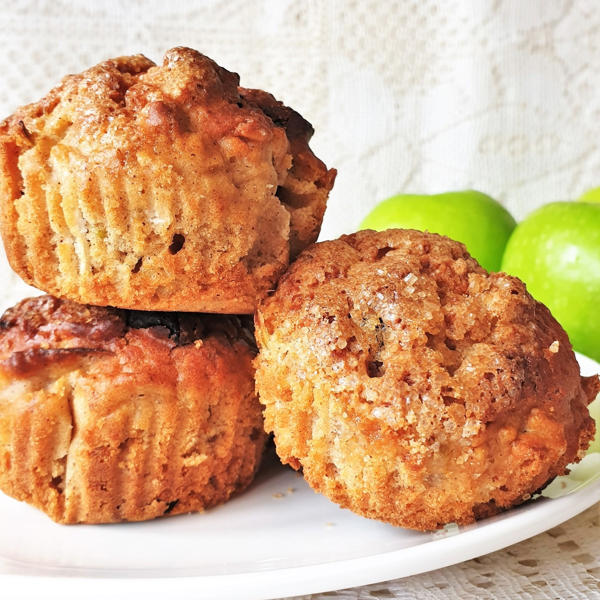 3 apple and oat muffins on a pile.