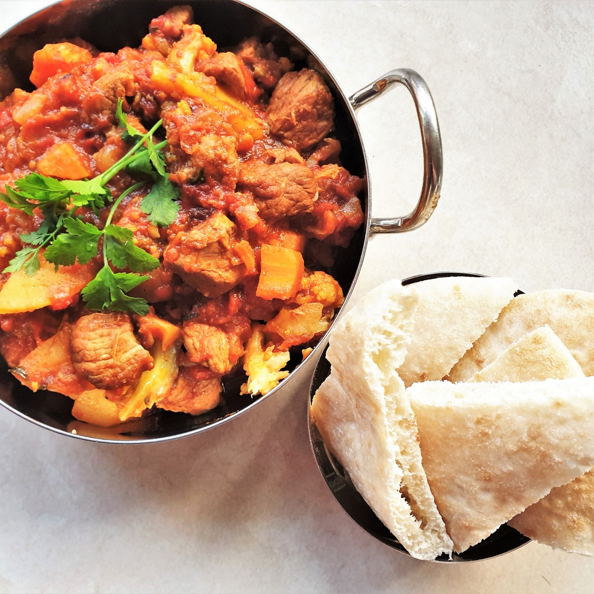 A balti dish of lamb curry alongside a slices of naan bread