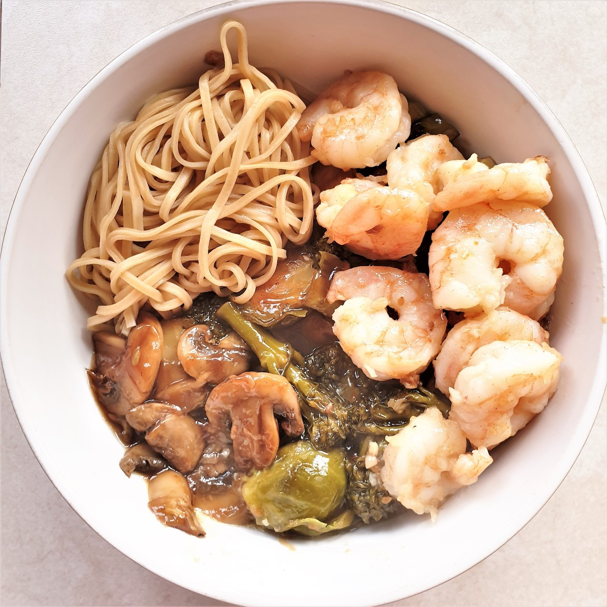 A bowl of honey garlic shrimp with saucy steamed vegetables and noodles.