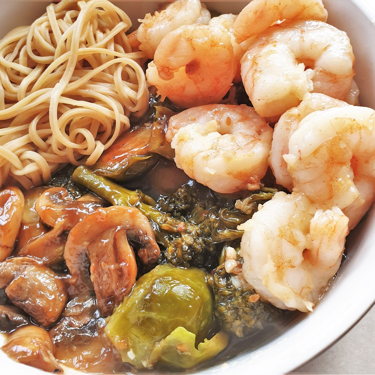 Closeup of a bowl of honey shrimp and steamed vegetables.