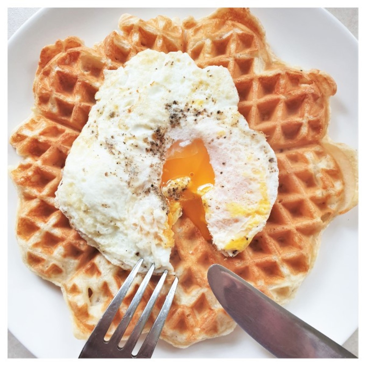 A fried egg with a runny yolk on a waffle.