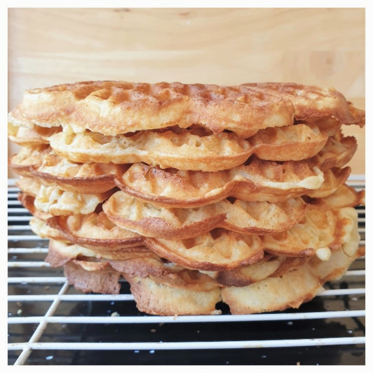 A pile of waffles on a cooling rack.