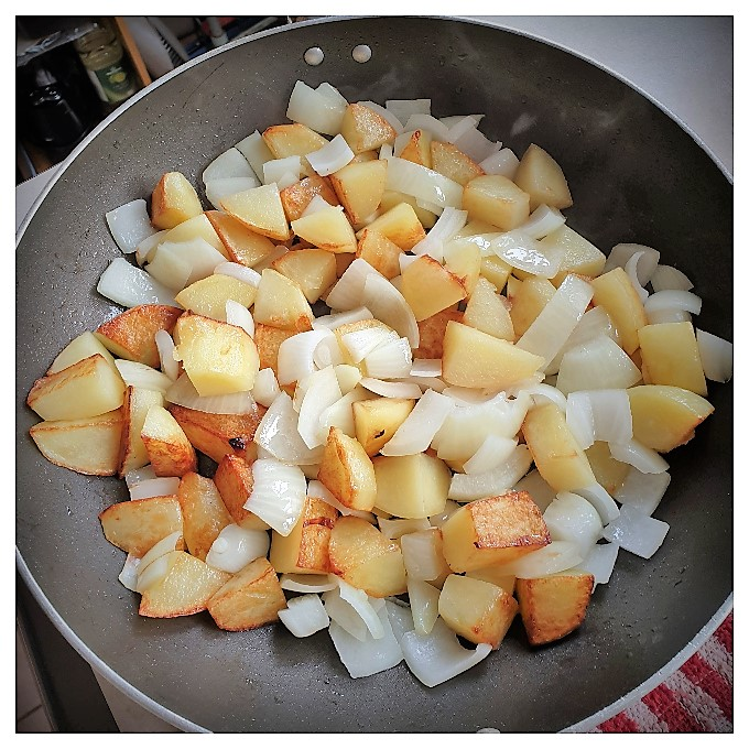 Potatoes frying with onions in a pan