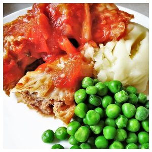 A plate of stuffed cabbage rolls with mashed potatoes and peas.