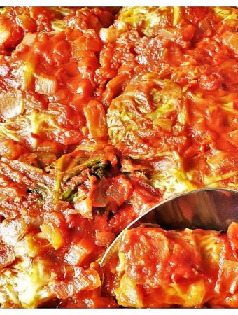 A dish of baked stuffed cabbage rolls with a spoon.