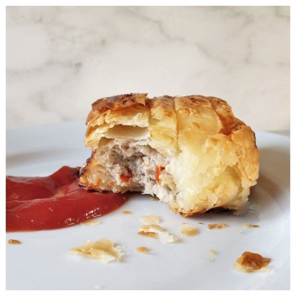 A pork and apple sausage roll on a plate with tomato ketchup.