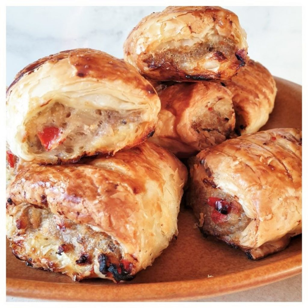 A pile of pork and apple sausage rolls on a plate.