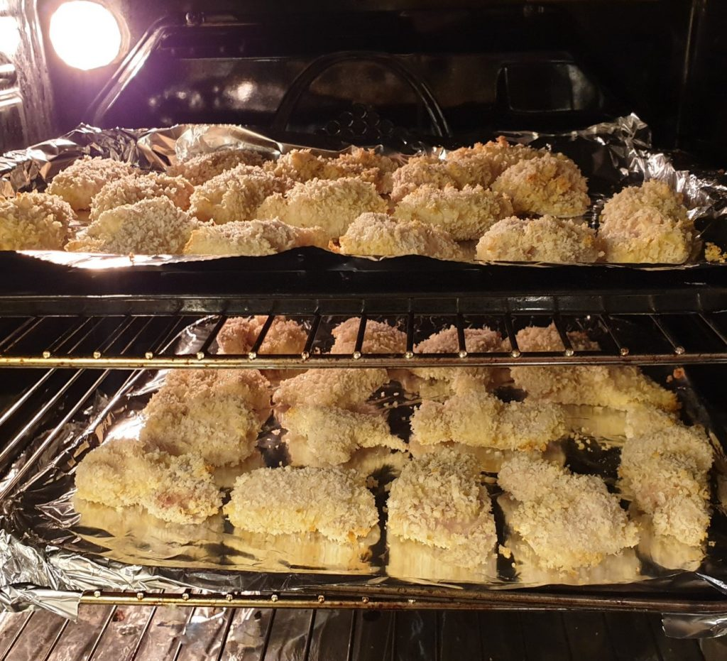 2 t4rays of crispy chicken baking in the oven