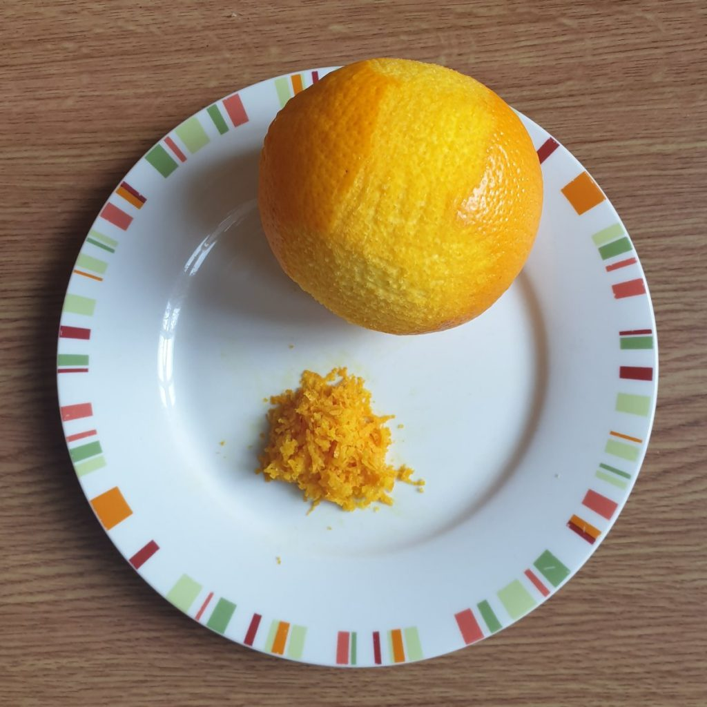 An orange on a plate with a pile of zest