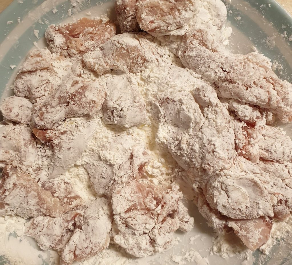 A bowl of chcken pieces covered in cornflour