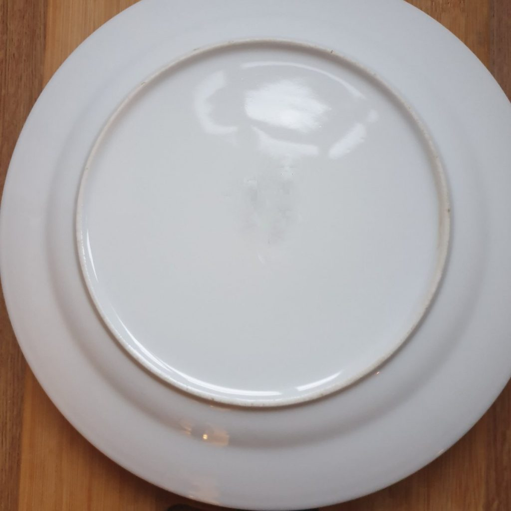 A plate upside down over a frying pan.