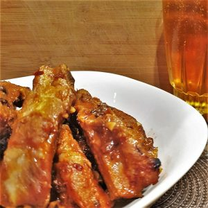 A plate of pork spare ribs next to a glass of beer.