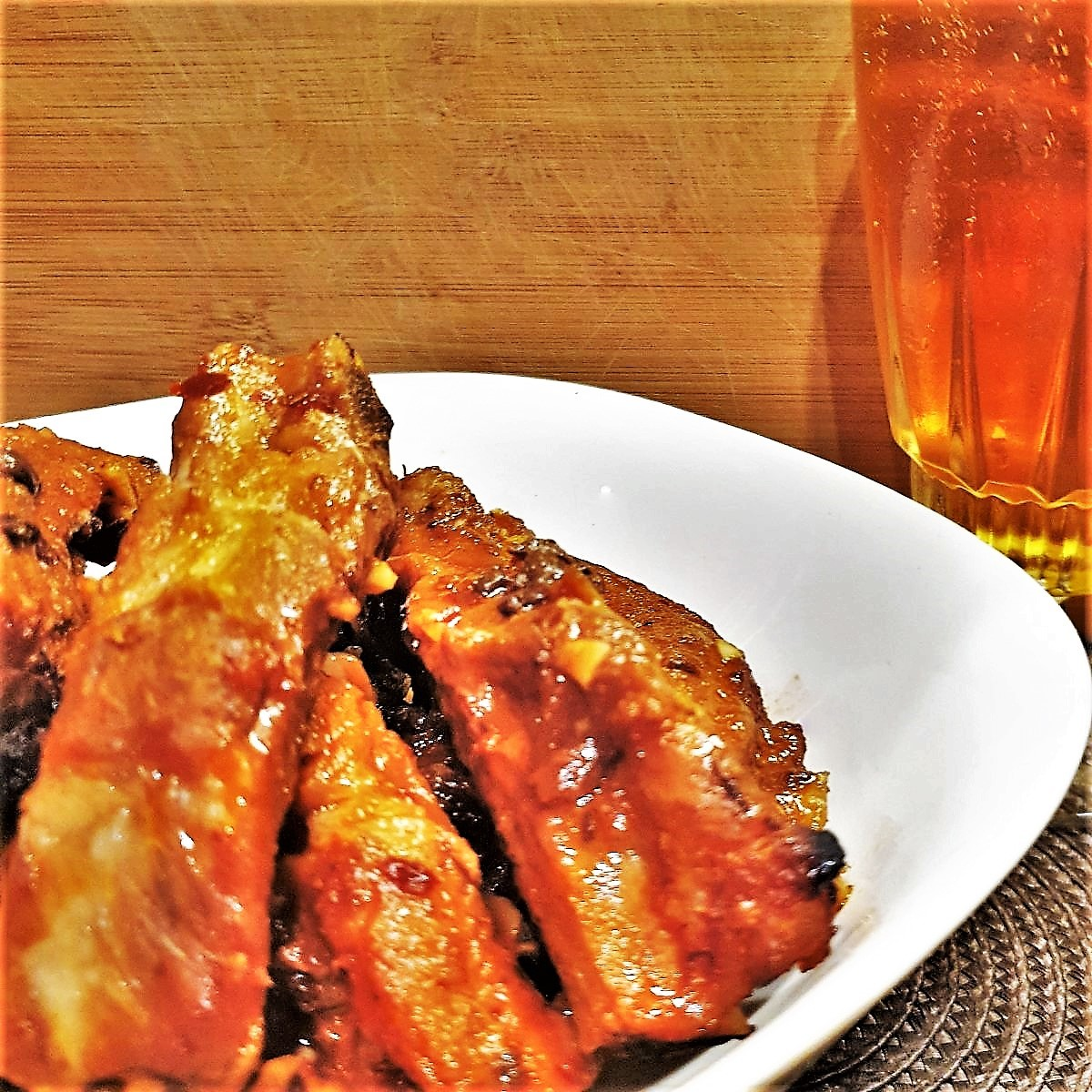 A plate of sticky pork ribs next to a glass of beer.