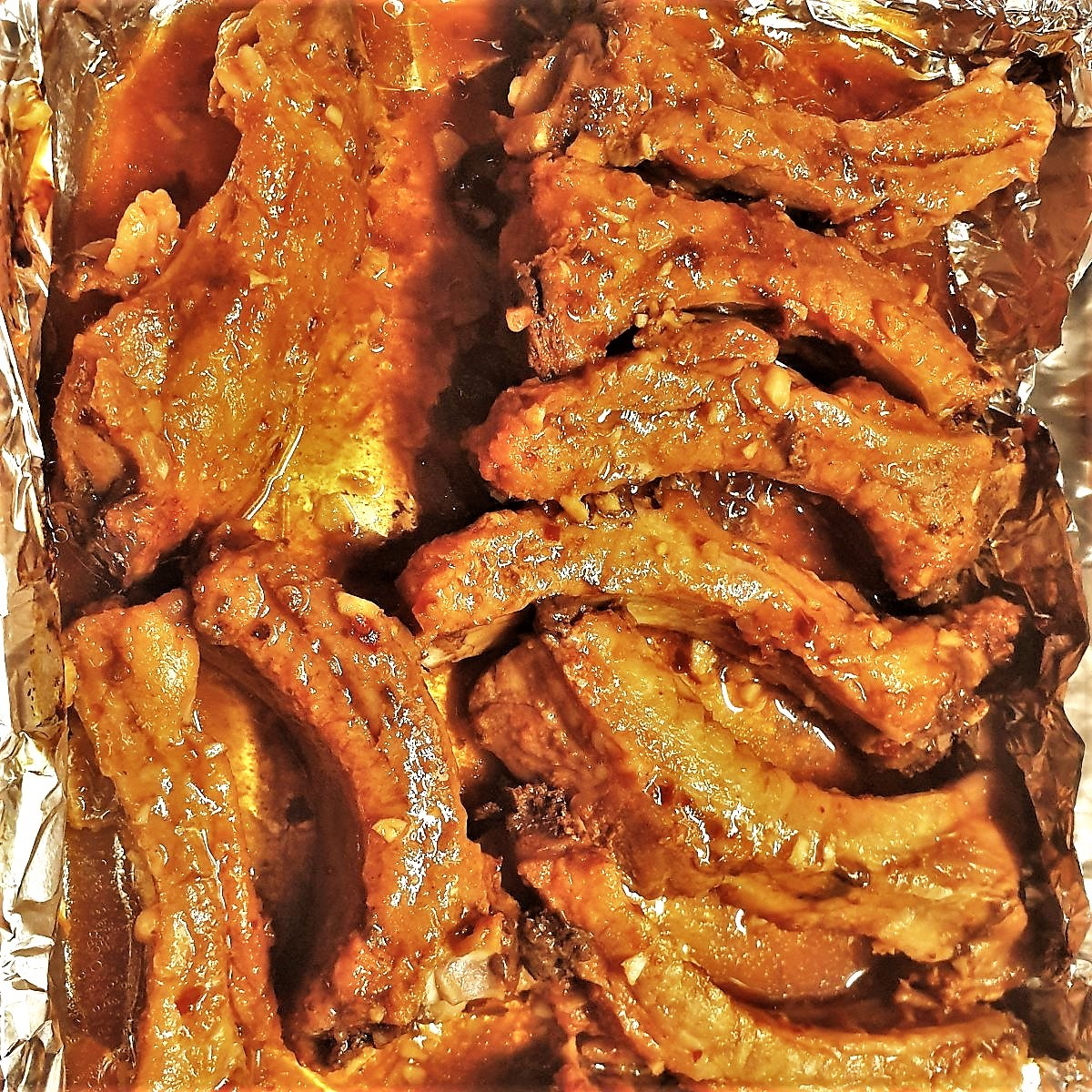Cooked ribs layered in a baking dish.