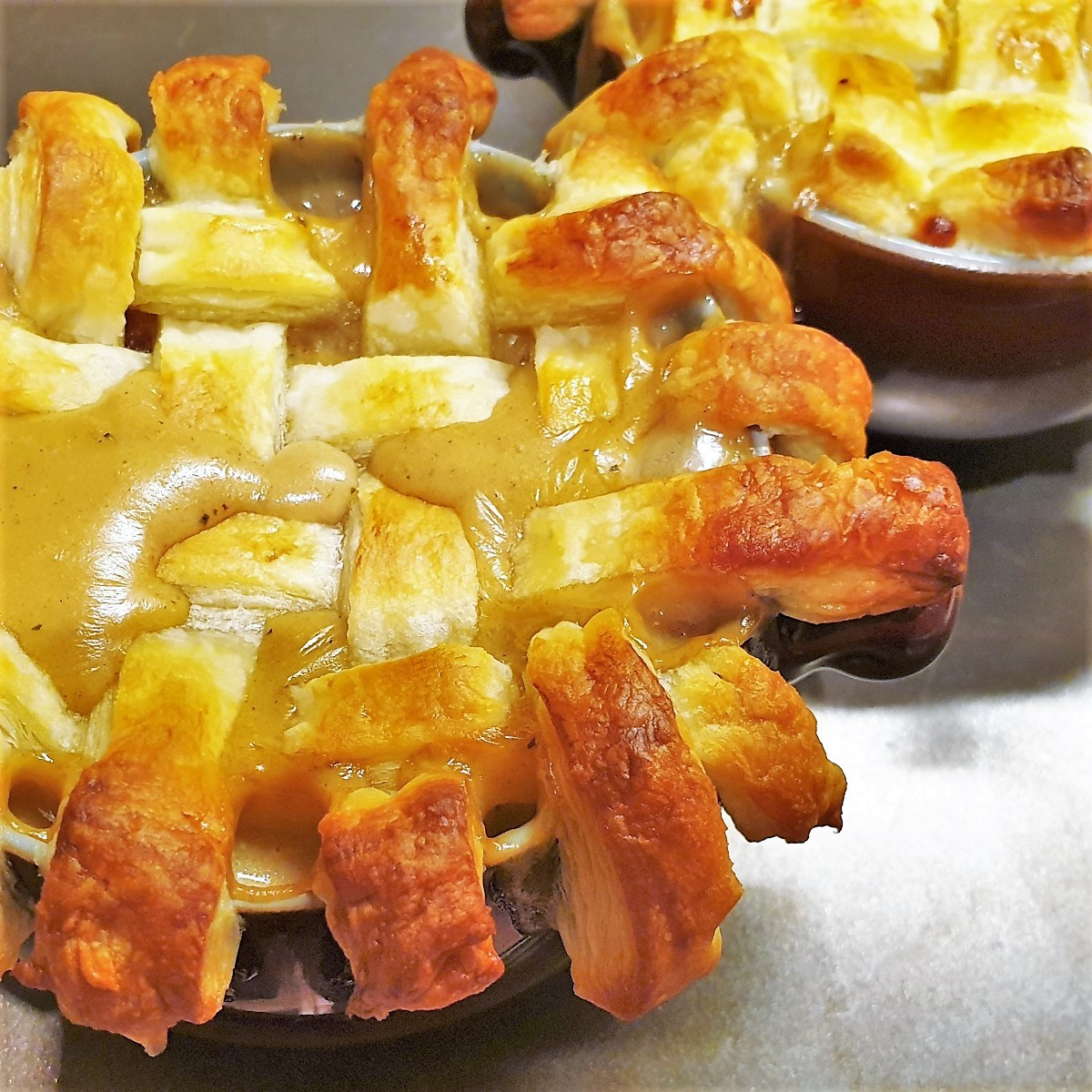 A beef pot pie topped with a lattice of puff pastry showing the gravy soaking through.