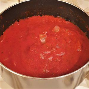 A saucepan of tomato and onion sauce.