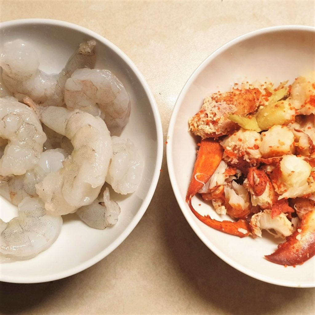 A bowl of shrimp and a bowl of lobster.