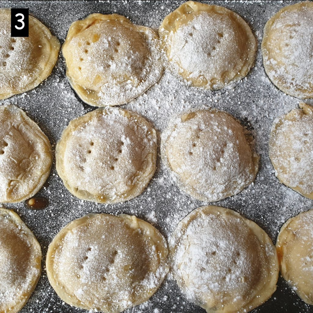A tray of Christmas mince pies sprinkled with icing sugar.