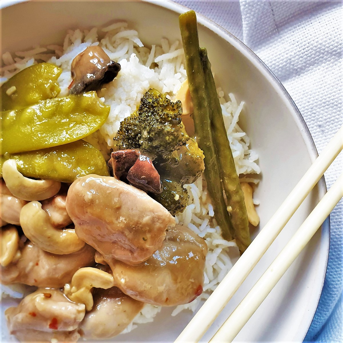 A dish of cashew nut chicken in a bowl with chopsticks.
