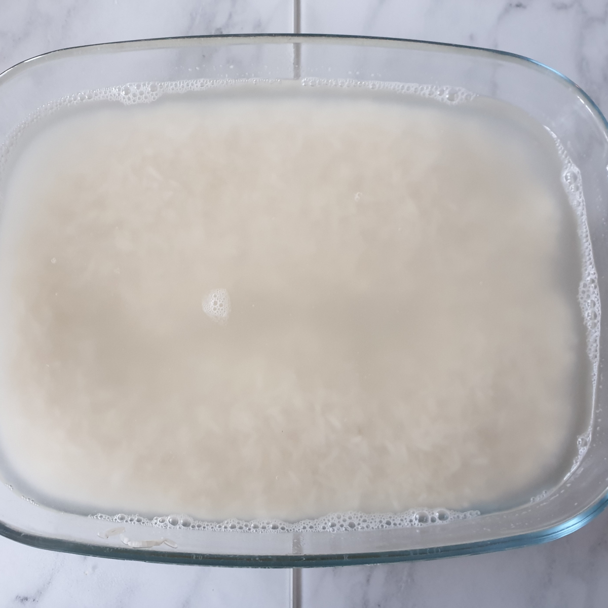A baking dish containing rice covered in water.