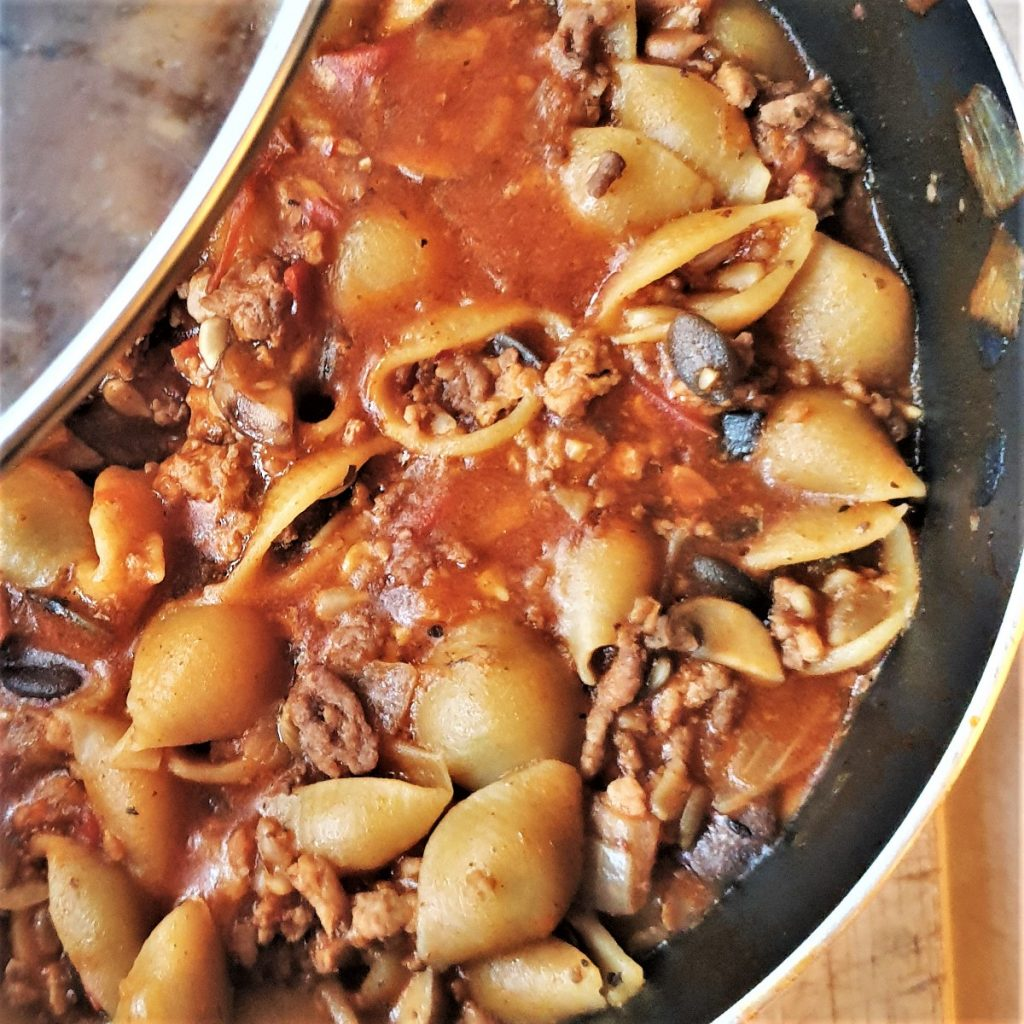 A dish of homemade hamburger helper pasta with tomato.