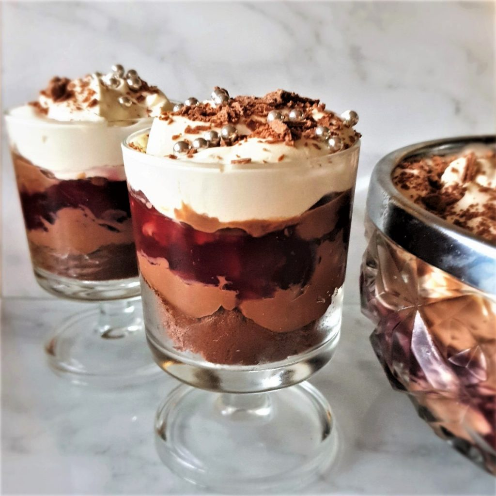 2 individual trifles next to a larger bowl of trifle.