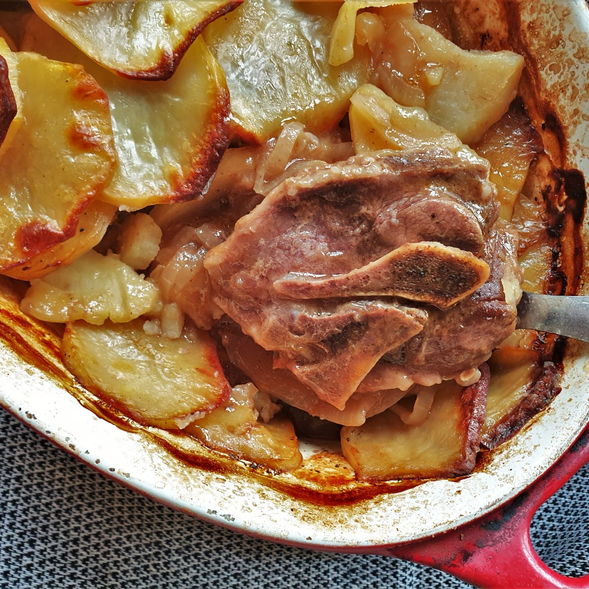 Lancashire hotpot showing a spoonful of lamb from under the potatoes.