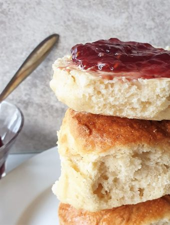 A pile of lemonade scones with the top one spread with jam.