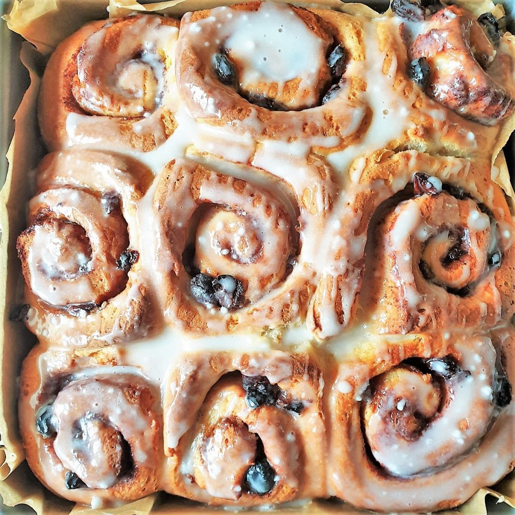 A tray of baked chelsea buns covered with glaze.