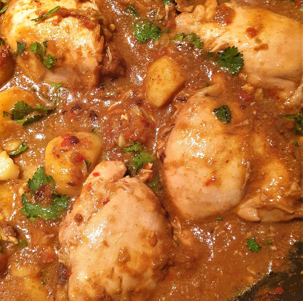 A close up of the chicken in the curry.