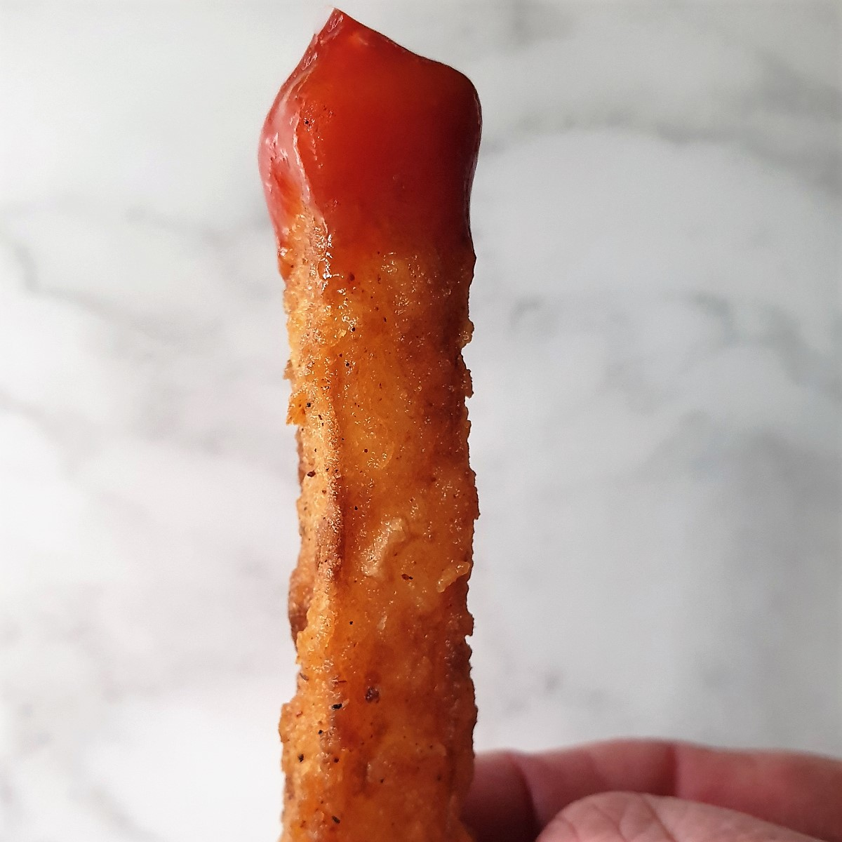 A crispy potato fry dipped in tomato sauce.