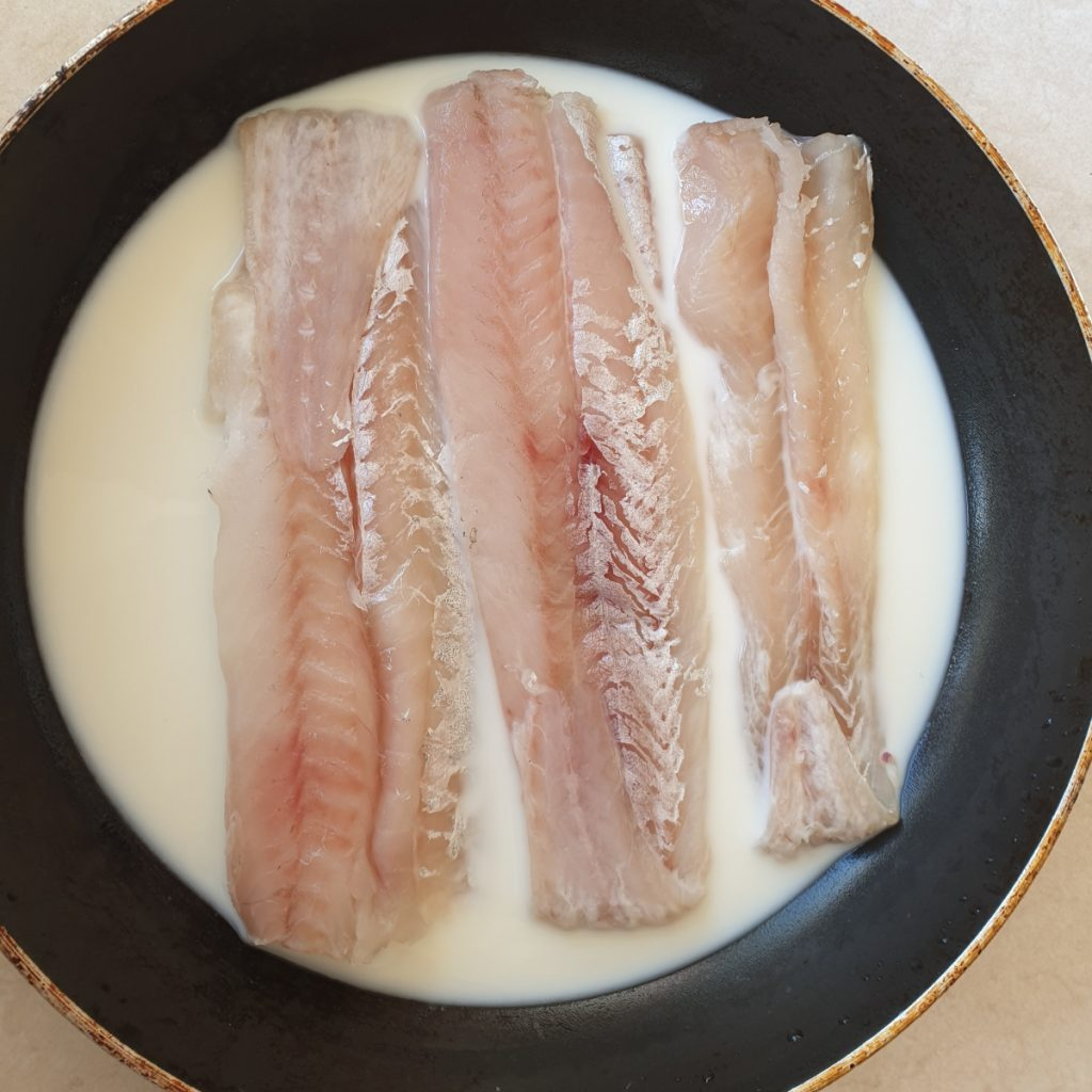 Three pieces of white fish poaching in a pan of milk.