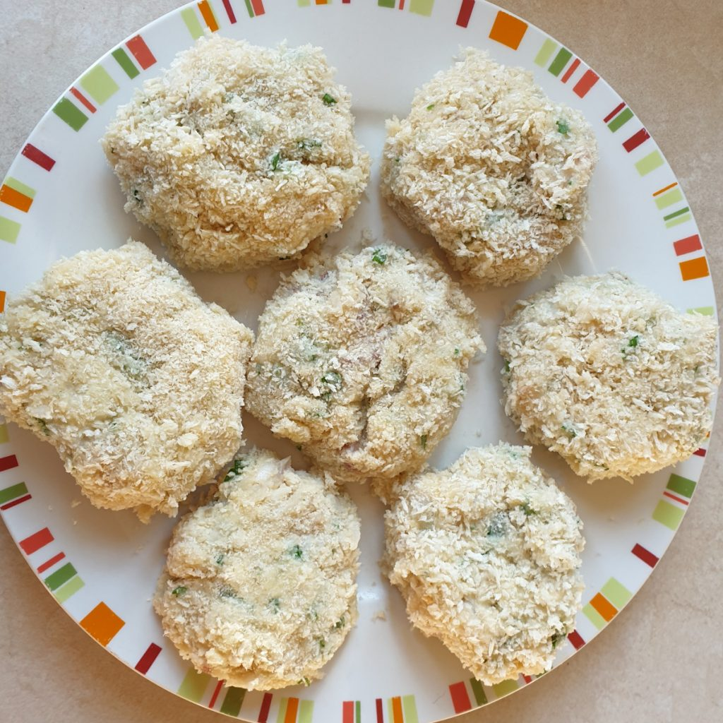 A plate of chilled coated homemade fish cakes.