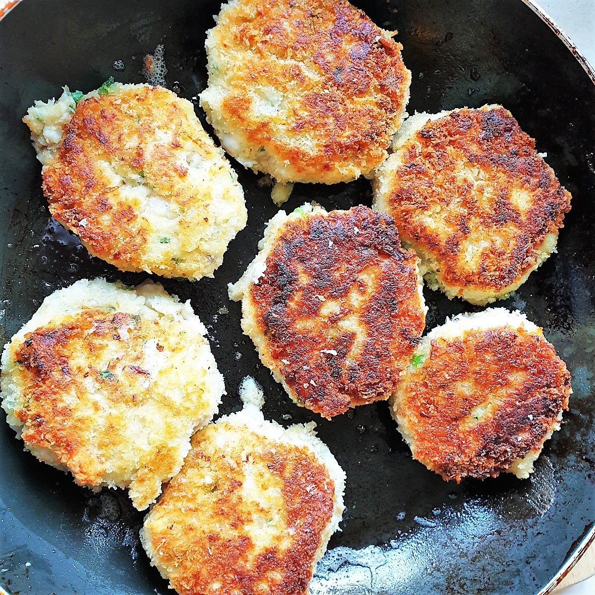 Fishcakes being browned in a frying pan
