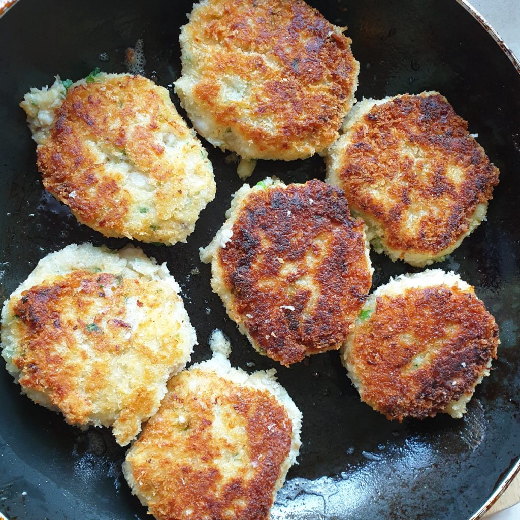 Seven homemade fish cakes in a frying pan.